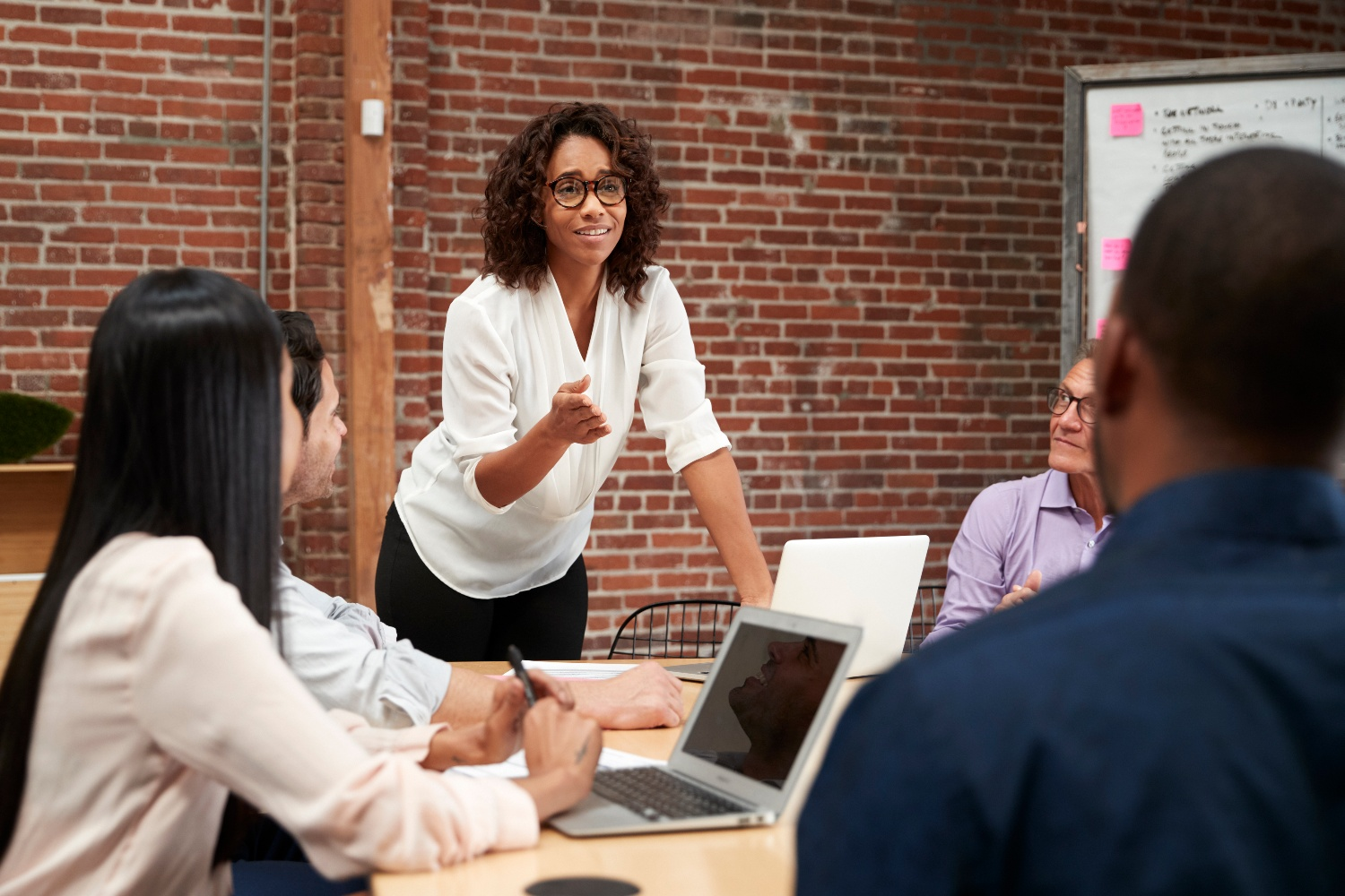 businesswoman-standing-and-leading-office-meeting--NVWRY95-1